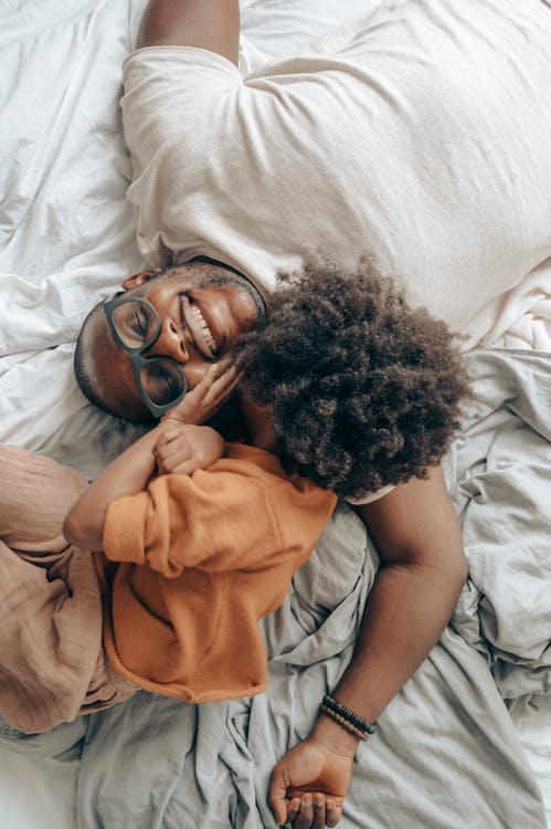 Cheerful black father and kid lying on bed