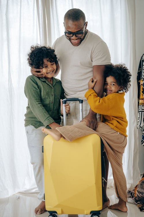Positive African American man in eyewear hugging with with kids with curly hair and standing near suitcase