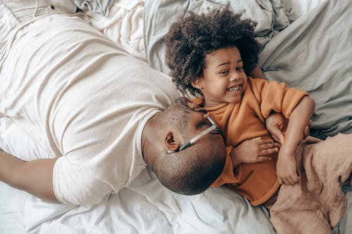 From above of cheerful African American man in eyeglasses and child with curly hair in sleepwear lying on bed