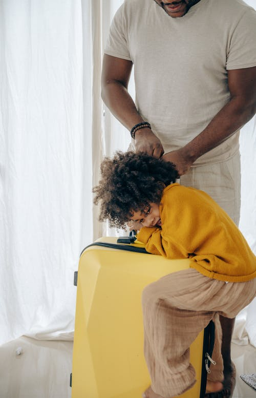 Crop black man with suitcase and kid at home