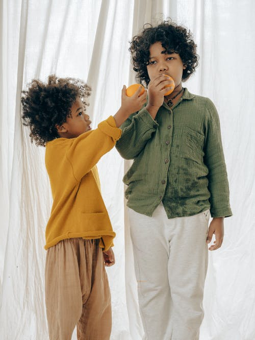 Adorable African American children in casual clothes standing near white curtain and eating orange during breakfast in cozy apartment
