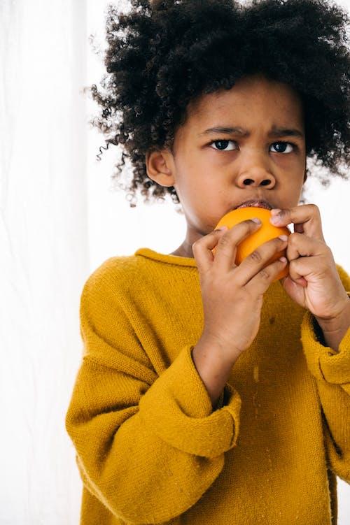 African American kid wearing yellow hoodie looking thoughtfully away while biting sweet ripe orange near white wall