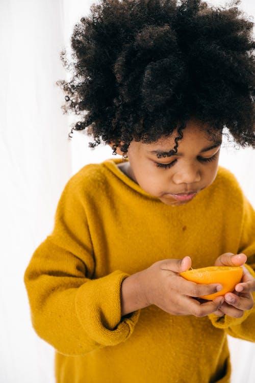 Amazed ethnic child with orange on white background