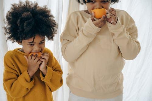 Ethnic children eating oranges on morning