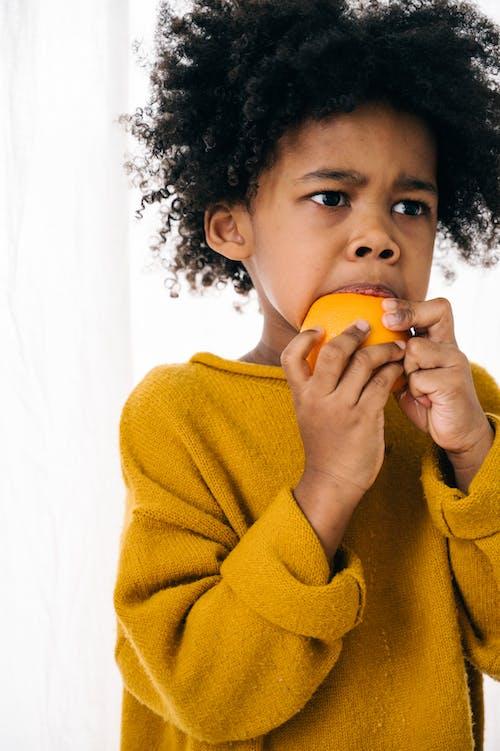 Kostnadsfri bild av afroamerikan, allvarlig, apelsin, äta