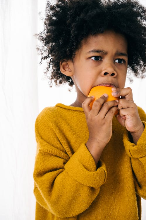 Adorable African American child in yellow hoodie looking away and biting ripe orange against white wall