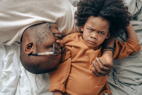 Ethnic father and kid relaxing in bedroom