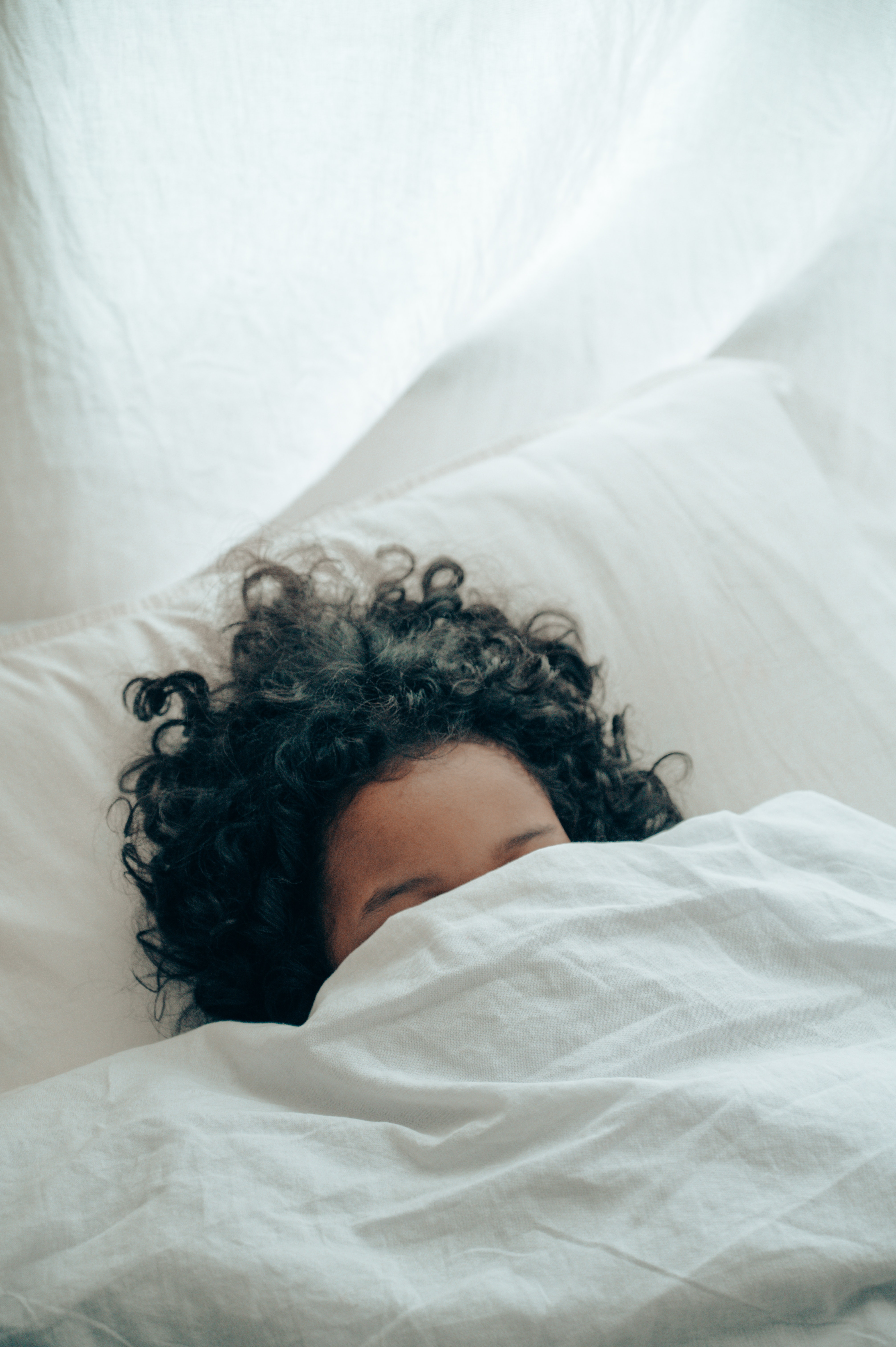 Woman in trying to sleep in bed with covers hiding her face.