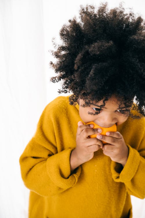 Cute African American curly kid with dark hair in vivid hoodie eating heartily fresh citrus while standing on white background