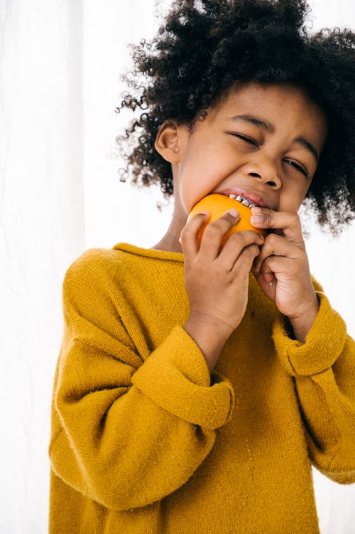 Black little child in yellow sweater eating orange half with squint at home against white curtain