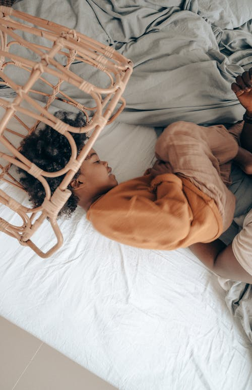 Black kid playing with dad on bed in laundry basket