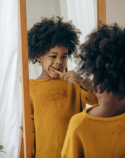 Black child brushing teeth in front of mirror