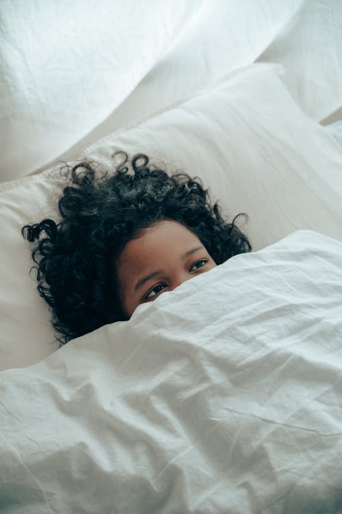 From above of unrecognizable ethnic kid with curly hair lying in white comfortable bed while covering lower part of face with  white blanket in light room