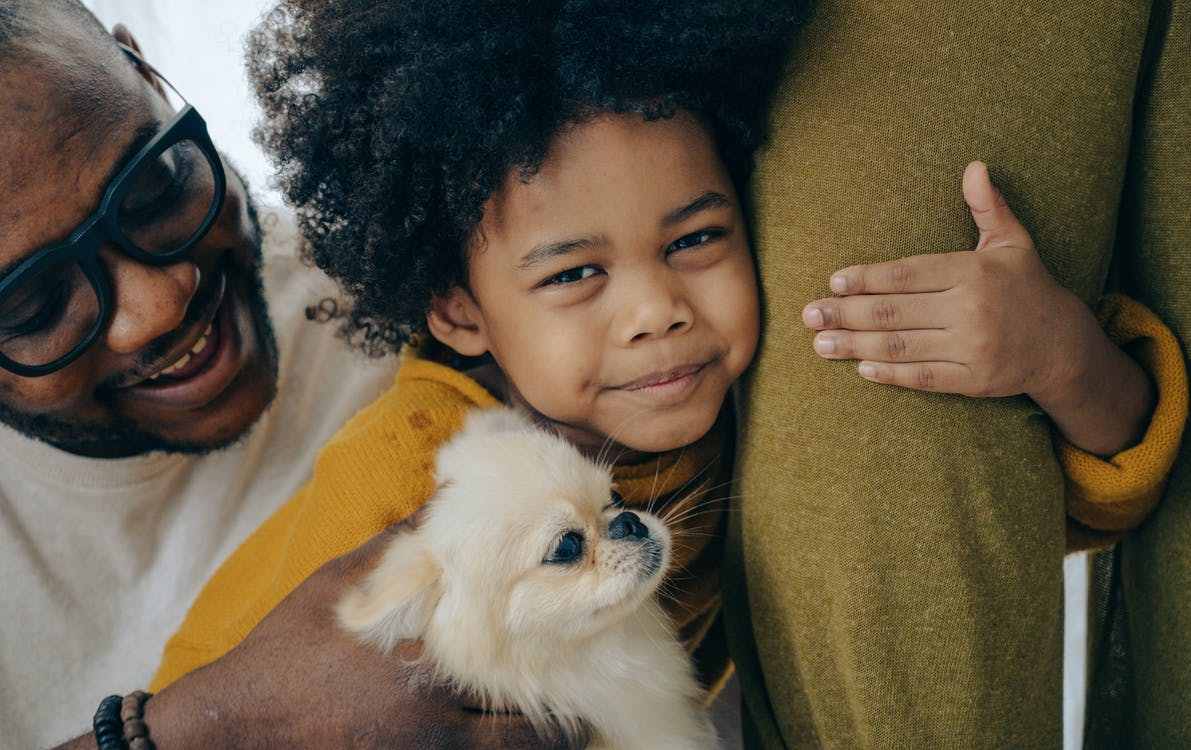 African American kid hugging dog and leg of parent