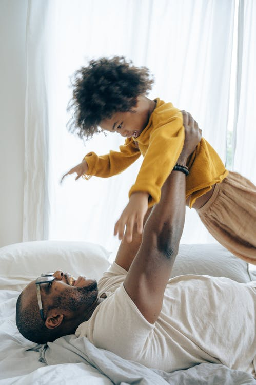 Side view of happy African American man in casual clothes lying on bed with raised up with hands child in light bedroom