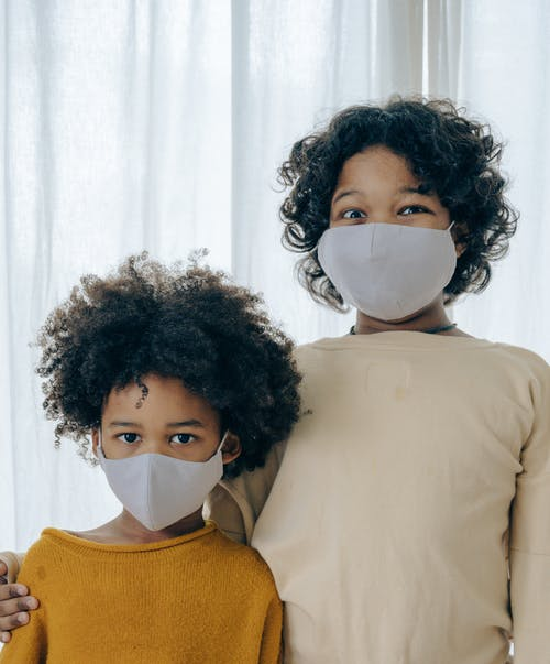 Ethnic children in medical mask against curtain