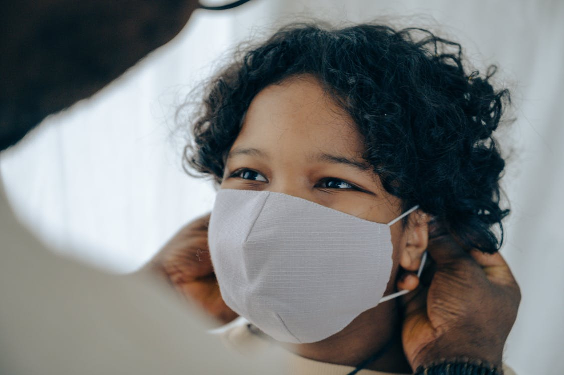 African American man helping positive little son to put protective face mask on during coronavirus outbreak
