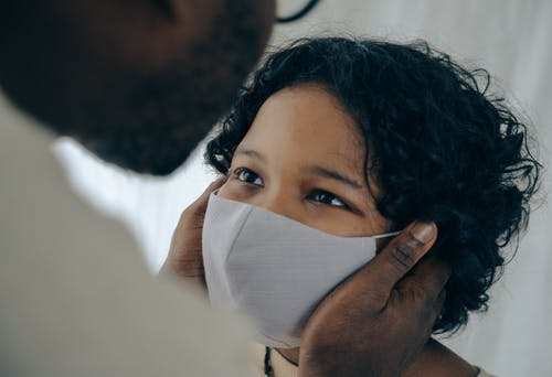 Father holding cheeks of son in face mask