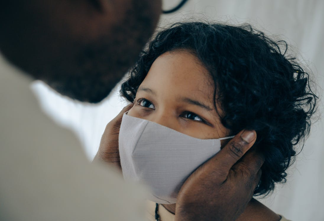 Black man in eyeglasses gently touching cheeks of cute calm little son wearing respirator during coronavirus pandemic