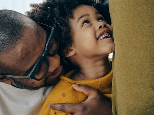 Crop cheerful African American man in casual shirt and eyeglasses hugging cute smiling son with curly hair in daytime