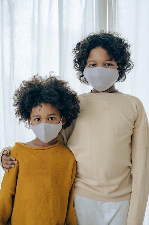 Cute positive bonding siblings in face masks