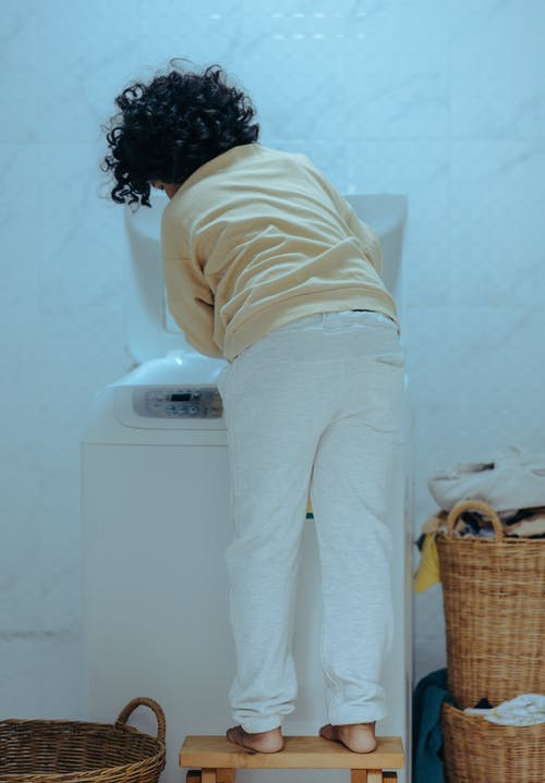 Back view full body faceless barefoot black kid putting clothes into modern washing machine while standing in laundry room near straw baskets with wash clothes