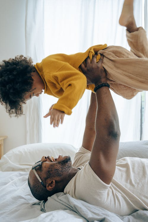 Father Playing With His Child in Bed