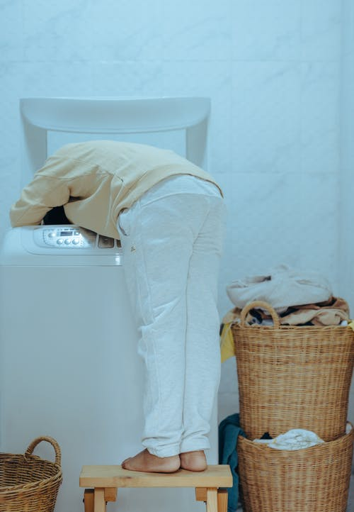 Back view full length barefoot faceless ethnic child in casual outfit standing on stool and taking clothes out of washing machine with top loader while keeping head inside of washer