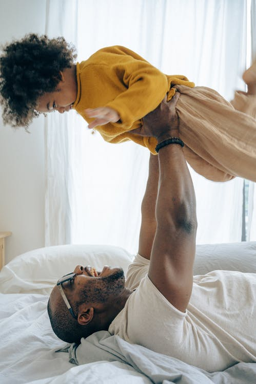 Delighted father lying on bed and lifting up happy son