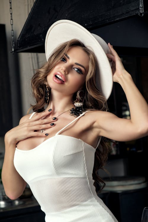 Stylish woman in hat and elegant white dress