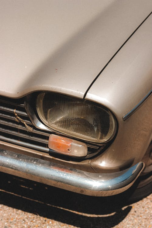 Headlight of old fashioned automobile parked on paved road on street in sunny day