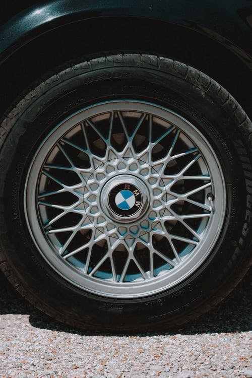 Contemporary design automobile wheel tire with symmetrical metal spokes on rim on shabby roadway