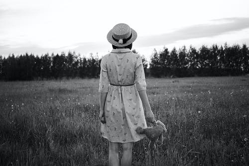 Black and white back view of faceless female in hat with soft toy standing on grass lawn in front of trees under cloudy sky