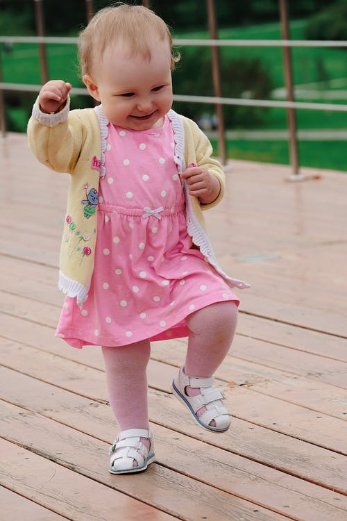 Full body of funny little girl in pink dress smiling and dancing on wooden terrace in green park