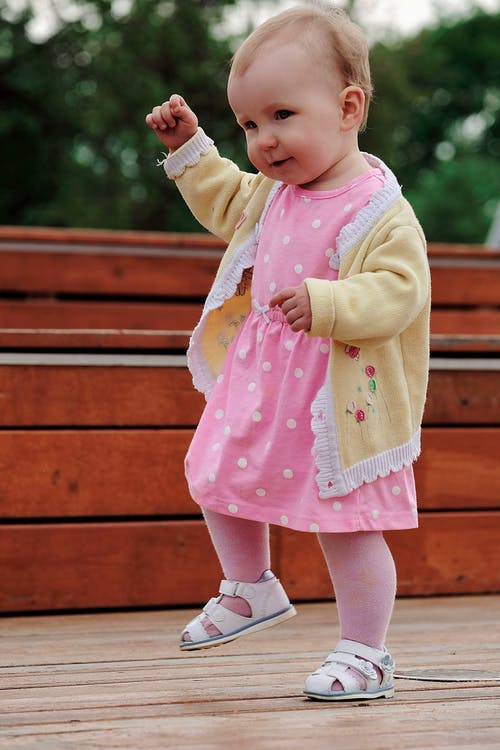 Side view of adorable little kid in pink dress doing steps in park on sunny day