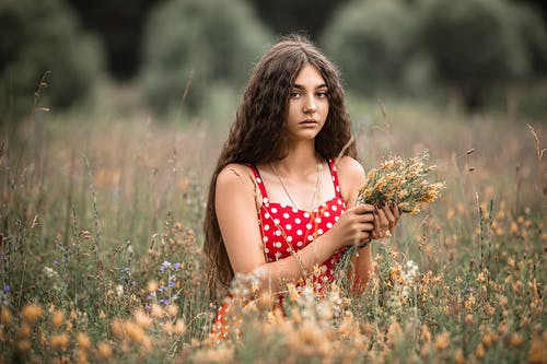 Charming woman with flower bouquet in field