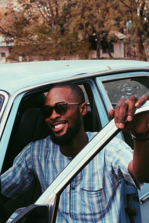 Happy black man near vintage car on street