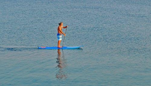Unrecognizable senior man on sup board on sea