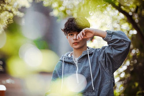 Thoughtful teenager covering eye with hand in park