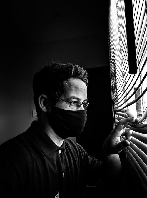 Anonymous man with mask and eyeglasses looking through jalousie in room