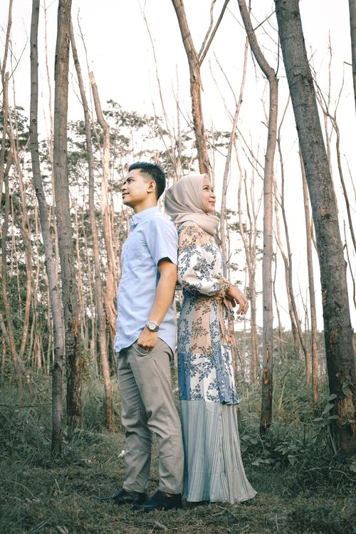 Happy ethnic couple standing back to back in forest