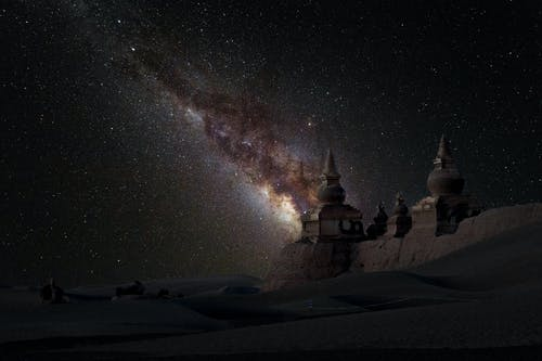 Fantastic starry sky over medieval architecture and snowy valley