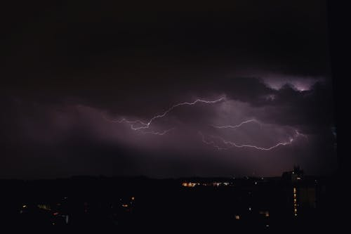 Powerful thunder and lightning flashing in dark purple night sky over city on rainy day