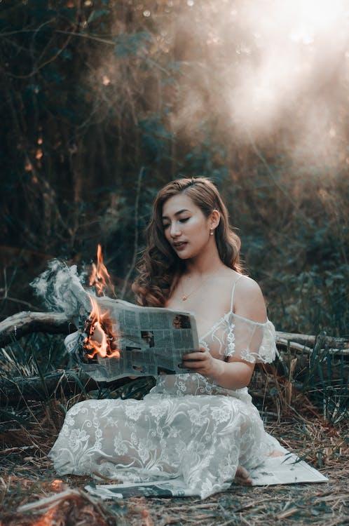 Mulher Com Vestido Floral Branco Sentada Na Rocha