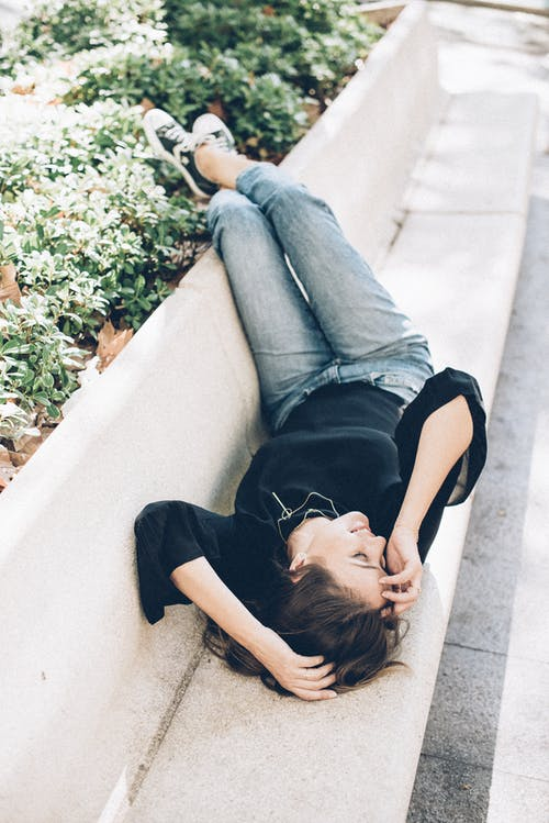 Woman in Black Shirt and Blue Denim Jeans Lying on White Concrete Bench