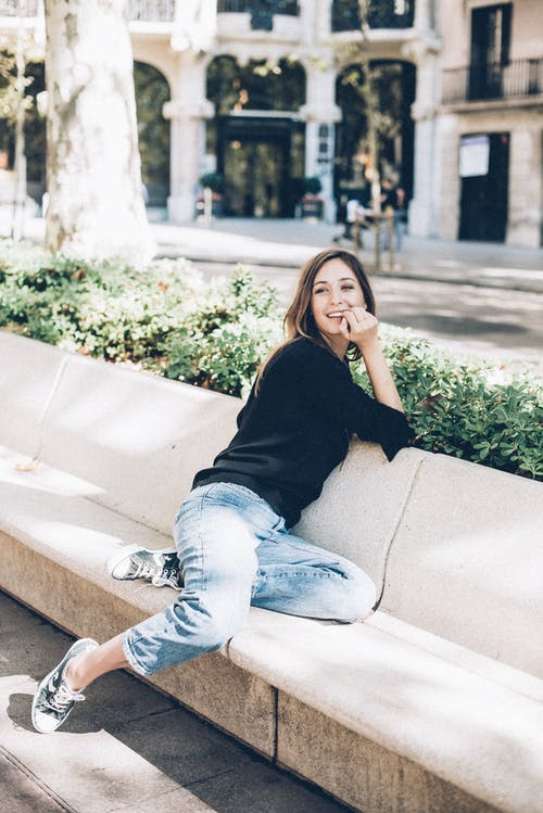 Woman in Black Long Sleeve Shirt and Blue Denim Jeans Sitting on White Concrete Bench during