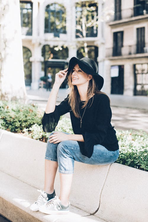 Woman in Black Long Sleeve Shirt and Blue Denim Jeans Sitting on Concrete Bench