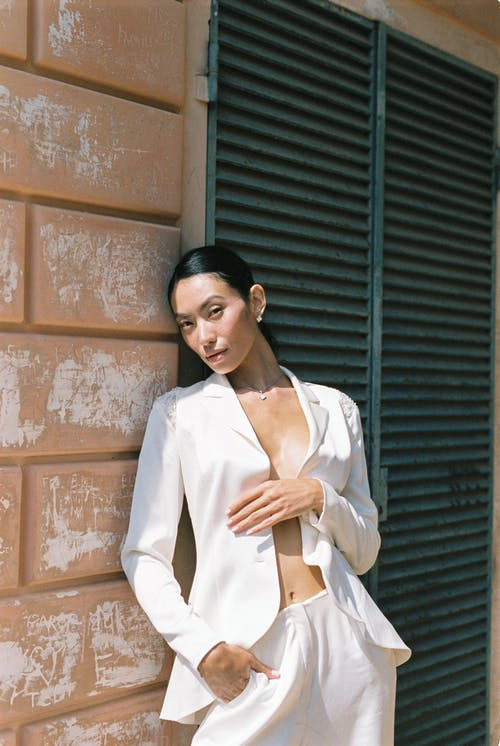 Woman in White Blazer Standing Beside Brick Wall