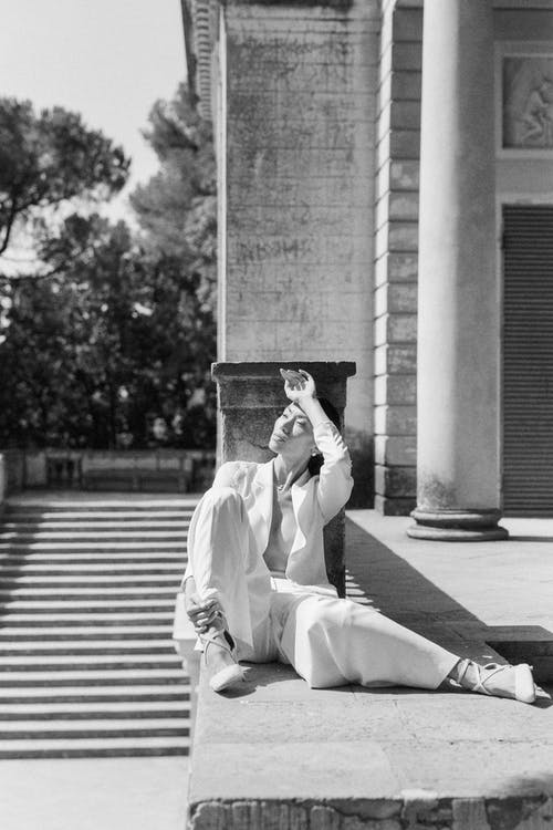 Man in White Robe Sitting on Concrete Bench