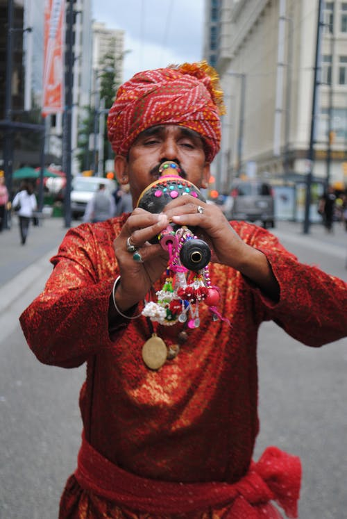 Concentrated adult Indian male in traditional clothes and turban playing folk pungi wind instrument while standing on street